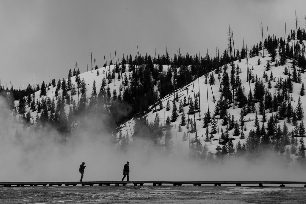People traversing the boardwalk that minimises damage to the geyser pools of the Grand Prismatic Spring.