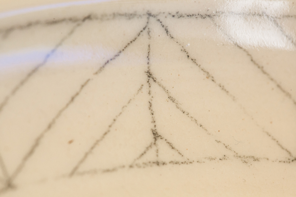 Image of hand-drawn decoration under glazed area of pottery, 2016