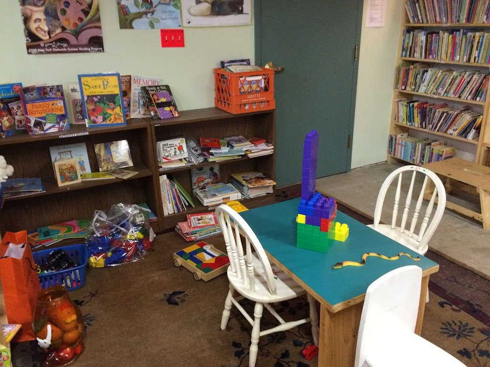 The kids area at the Friends of Schroon Lake Library Book Store. No, its not a real snake! Photo: Schroonlake Collection. Copyright 2015.