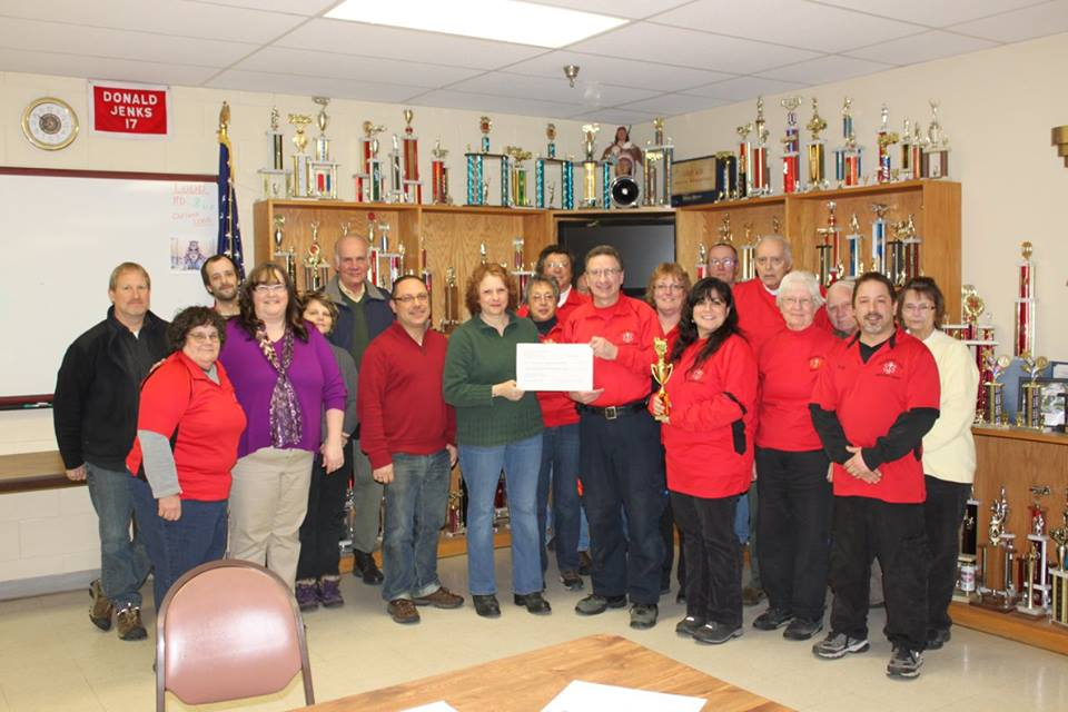 Shelby davis presents a check to the schoon lake ems squad in 2015