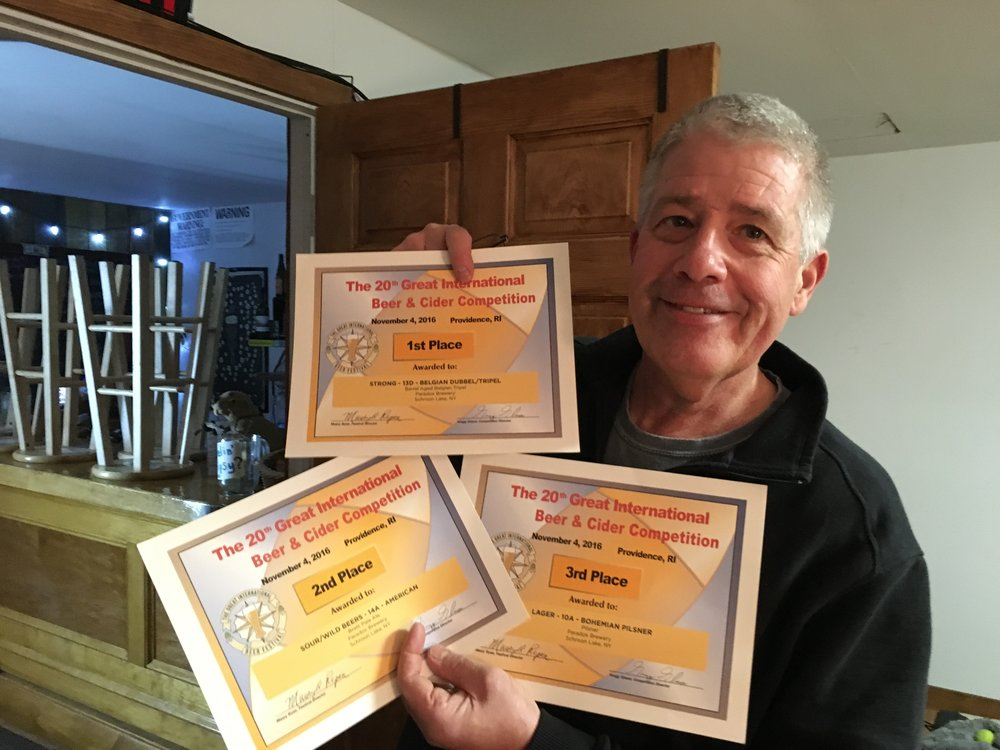 Paradox Brewery President Paul Mrocka with a handful of recent awards for his beer