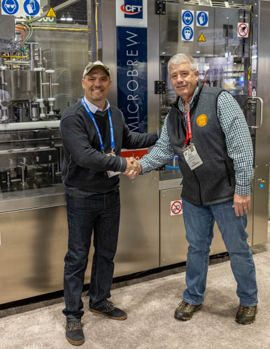 Paul Mrocka meeting David Garab, Regional Sales Manager at CFT Packaging USA in front of the new canning line, on its to the North Country.
