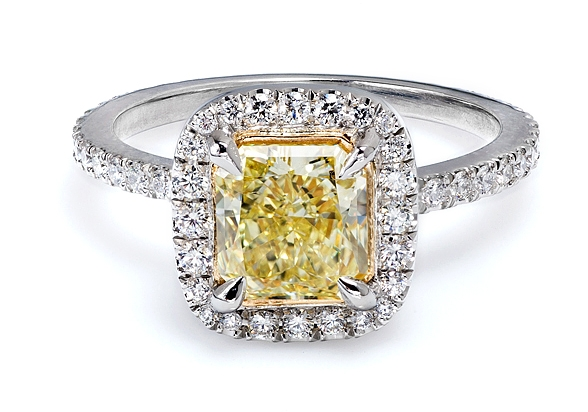This custom made Platinum Anniversary three stone diamond ring was made for Andrea P. to celebrate a wedding anniversary. Cushion cut diamond weighting 1.05 carat, G color, VS1 clarity, GIA certified, in the center flanked by two half moon diamonds and diamond pave on the shank of the ring. Just one outstanding example of the rare yellow diamond being used in engagement rings.