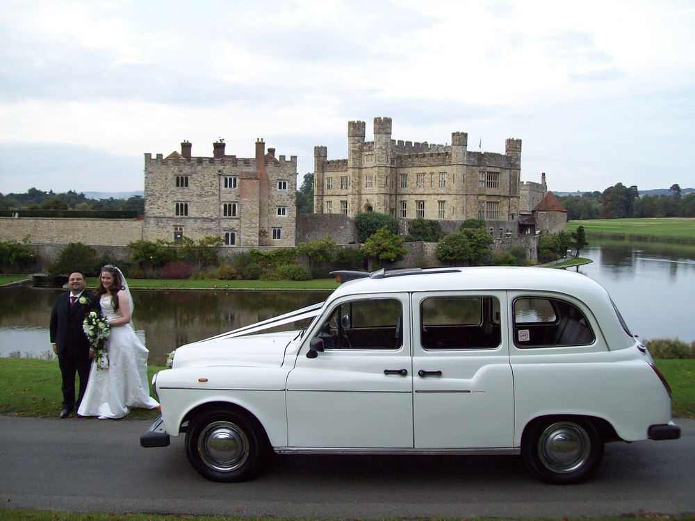 The white London Taxi is a wedding car in Kent, pictured here at Leeds Castle.