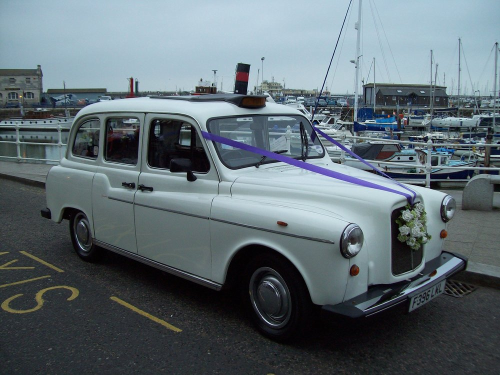 white wedding taxi pictured at Ramsgate Harbour which transferred 5 bridesmaids plus mum to the service before returning for the bride.