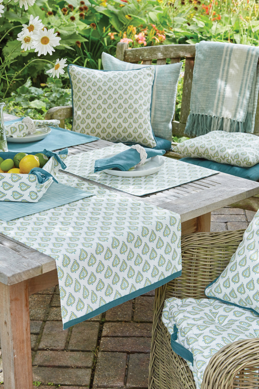 'Les Indiennes'   A wood block inspired print on 100% porcelain coloured cotton, this collection features cool lagoon shades;teal and a relaxed ochre. Accompanying plain fabrics and indoor/outdoor woven placemats complete a fresh summer look.