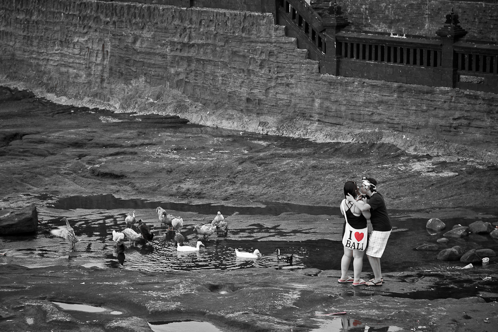 Young couple kissing by water in Bali, Indonesia