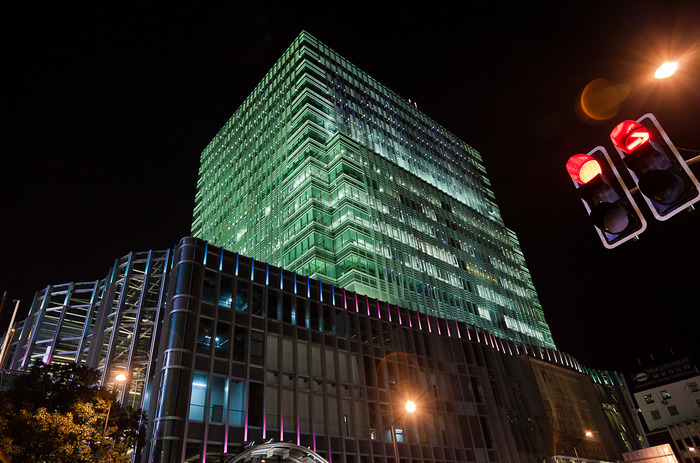 Night time photo of illuminated building at intersection near Nanjing Road in Shanghai, China
