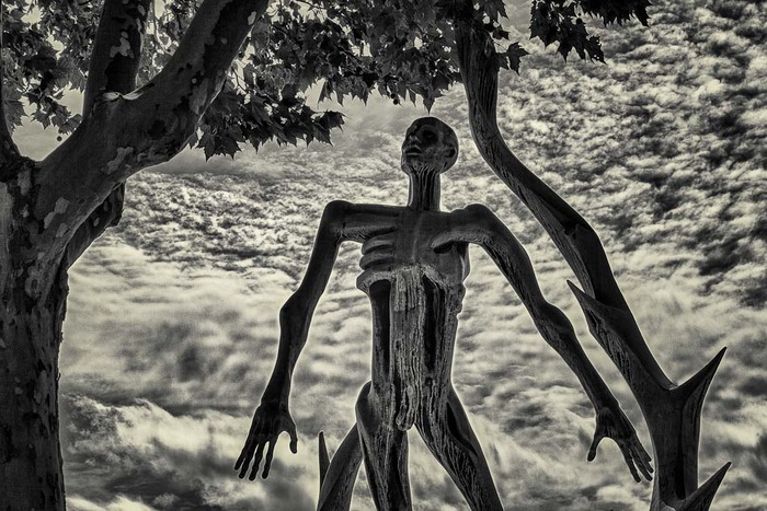 Surreal photo of statue against brooding sky at Pere Lachaise Cemetery, Paris, France