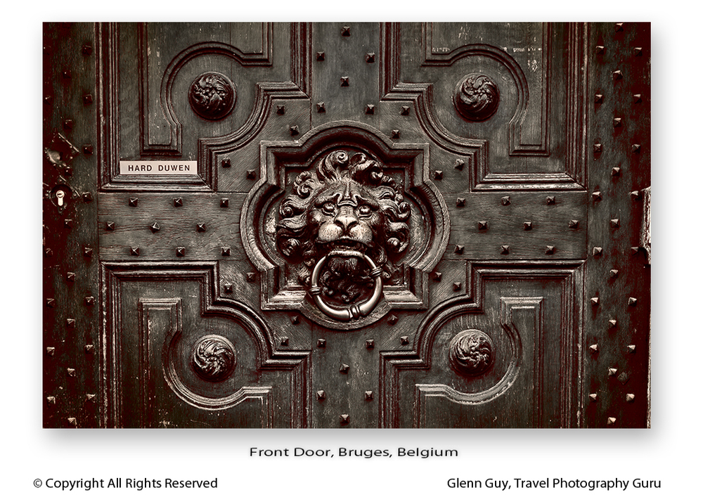 A detail of a beautifully ornate wooden front door in Bruges, Belgium