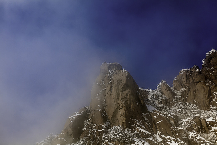 mist clears to reveal rocky mountain outcrop on Huangshan, China