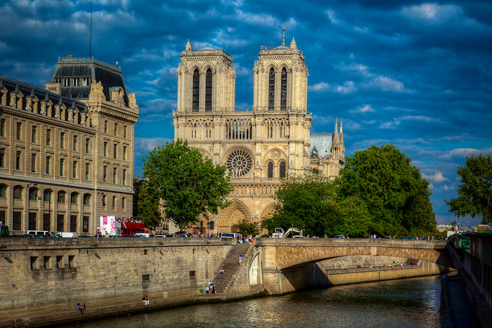 A lovely view of Notre Dame Cathedral, bathed in warm late afternoon light, with La Seine in the foreground