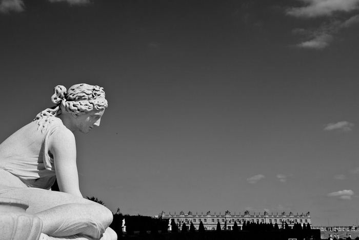 Black and White photo of a female statue in the foreground set against the Palace of Versailles