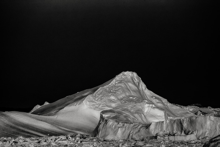 This contemporary black and white photo depicts the quiet solitude of a huge iceberg near Ilulissat, Greenland