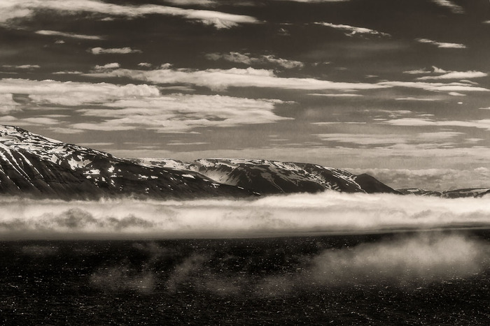 Low lying clouds, just above the sea and in front of a distant mountain range in Iceland