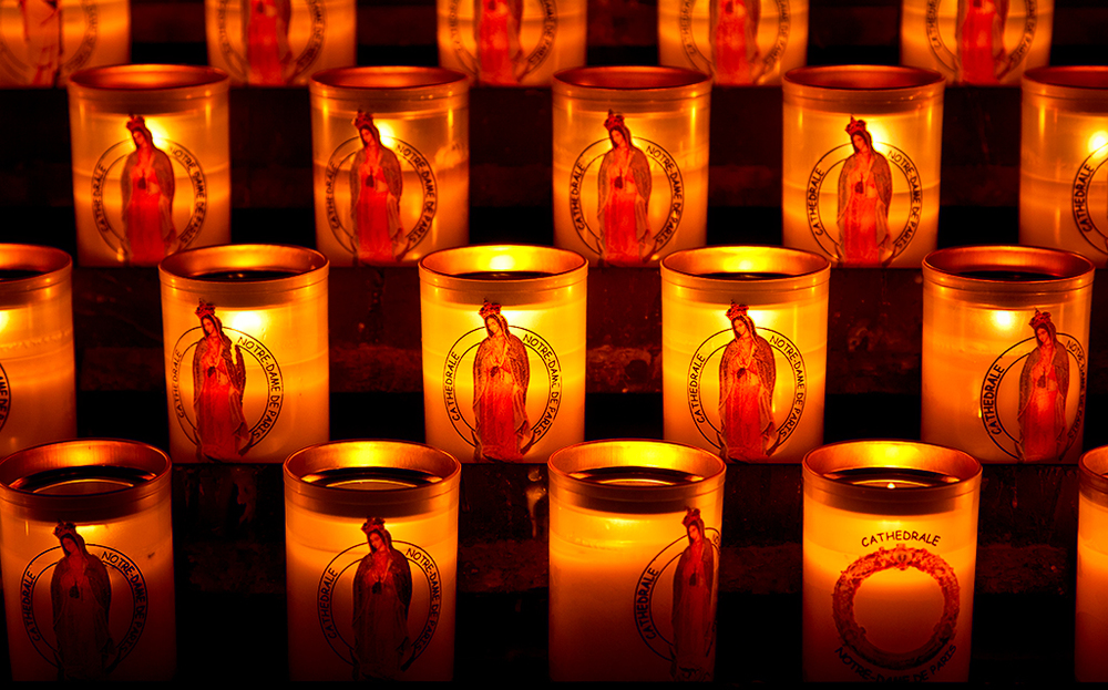 Close up of lit candles in Notre Dame Cathedral Paris, France