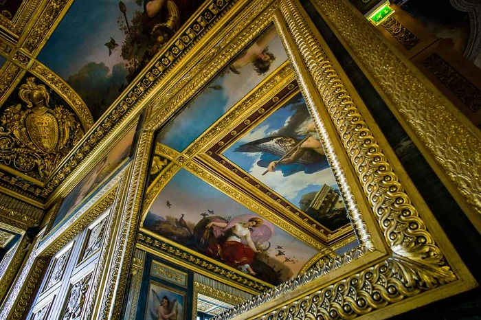 Reflection of surrounding paintings in mirror at the Palace of Versailles, France