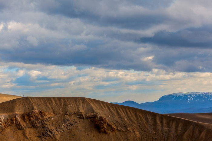 Person standing atop Stora-Viti crater, Iceland in front of an approaching storm