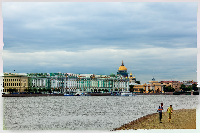 Two people walking by the Neva River with the historical city of St. Petersburg, Russia behind