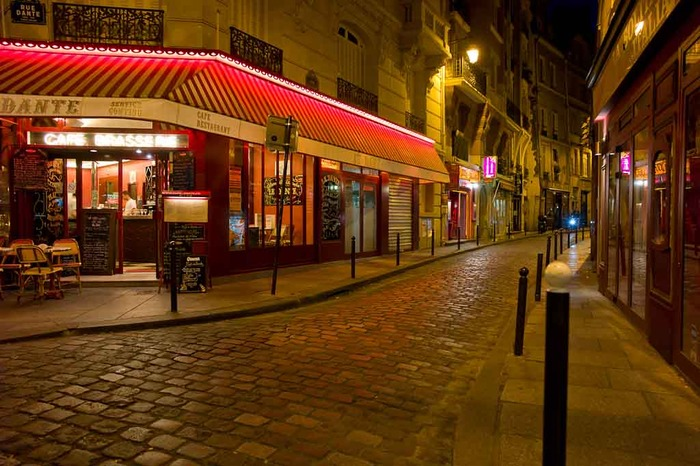 This night time photo of a cobbled street scene in Paris, France is full of nostalgia