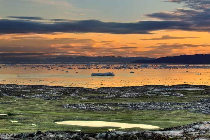 Photo depicting the view down to the icefjord, at sunrise, near Illussiat in Greenland