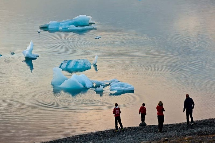 Family gazing at ripples in water and icebergs at Jökulsárlón (glacier lagoon) in Iceland