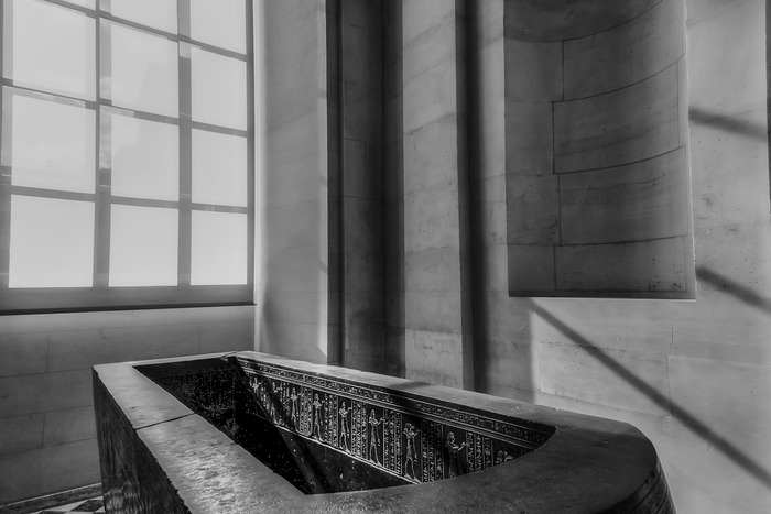 A black and white photo of a sarcophagus in the Louvre, Paris