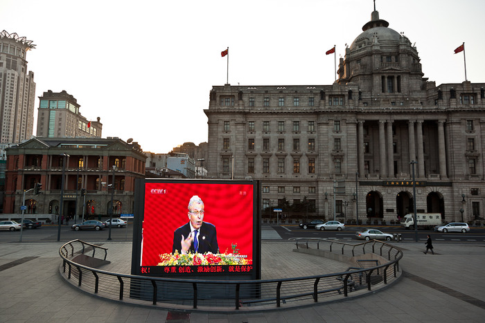 Large TV screen in front of historical building on the Bund in Shanghai, China
