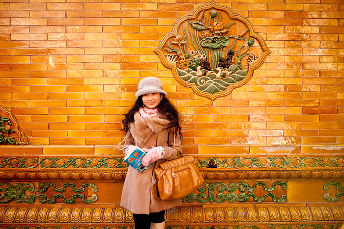 Beautiful Chinese girl and yellow and orange brick wall at the Forbidden City in Beijing, China