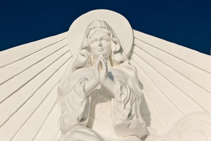 Statue of Mary, mother of Jesus, against blue sky at Snowworld in Harbin, China