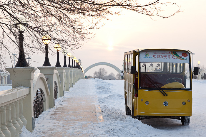 Tourist bus, parked on bridge, outside front entrance of SnowWorld in Harbin, China