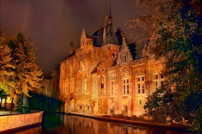 Beautiful warm artificial light illuminates a building on the canal during a warm summer's evening in Brugge, Belgium