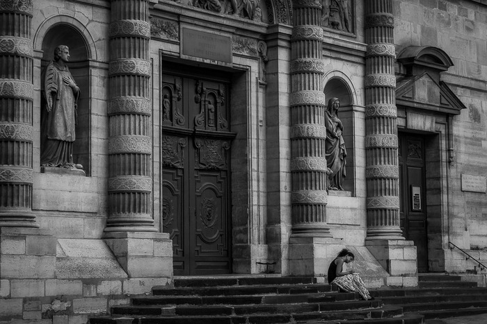 A young woman writing in a diary in front of a beautiful church facade in Paris, France