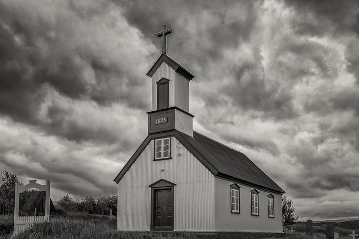 Black and White photo of dramatic clouds over picturesque church in rural Iceland