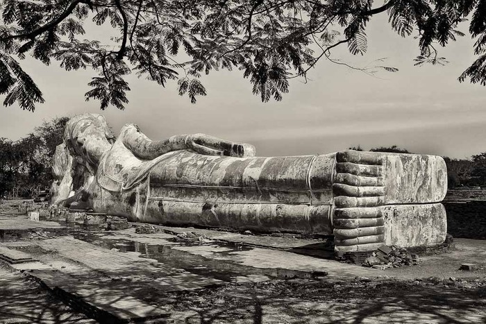 Black and white sepia-like image of the reclining buddha statue outdoors in Ayutthaya, Thailand