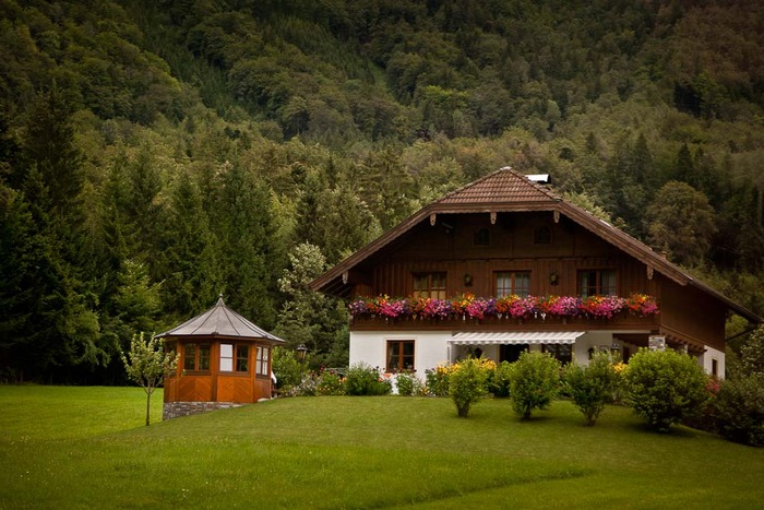 Classic Austrian farmhouse in the mountains near Salzburg, Austria. Flower boxes can be seen on the upstairs balcony