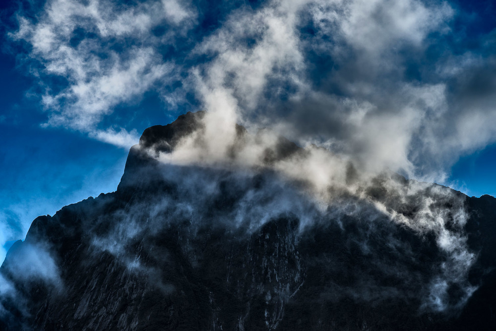 A spectacular scene as    light illuminates clouds    in front of a mountain top above    Milford Sound, New Zealand   .