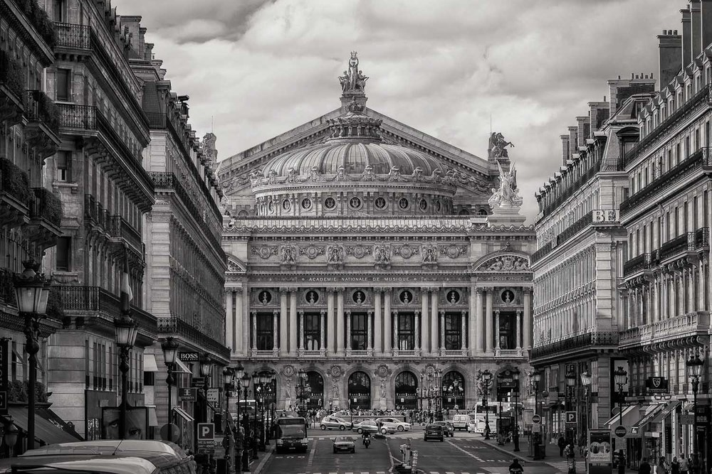 A contemporary B&W rendering of a Paris Street scene, looking onto the Academie Nationale De Musique, evokes a sense of nostalgia in one of the world's most beautiful cities. Canon 5D Mark II camera and Canon 70-200mm f4 IS L series lens @ 138mm.Exposure: 1/500 second @ f11 ISO 400.