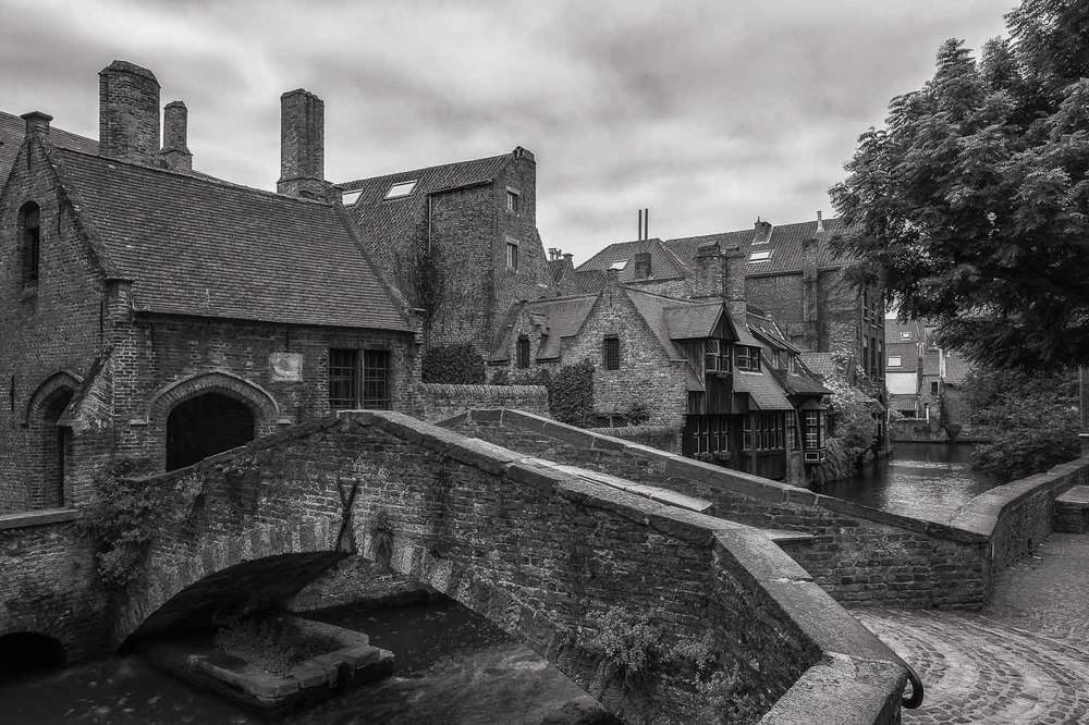 Shapes and texture dominate this black and white photo of a footbridge crossing a canal in the historical city of Brugge, Belgium.
