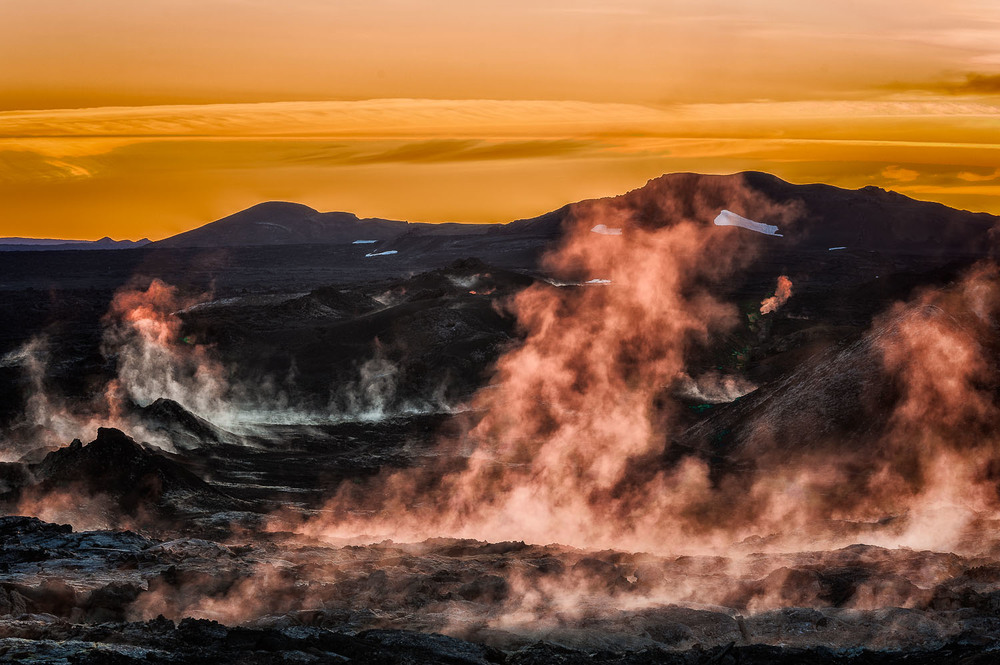 Steam, venting from the black earth at sunrise, makes for a dramatic and eerie view of the Leirhnjukur Lava Fields near Myvatn in Northern Iceland.