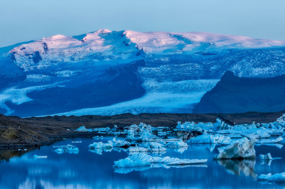The last light of a beautiful sunset touches a distant mountain while the rest of the scene is bathed in the cool blue light of dusk at Jokulsarlon Glacier Lagoon in Iceland.