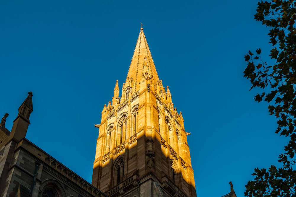 Sunlit spire set against a blue sky at St. Paul's Cathedral Melbourne.