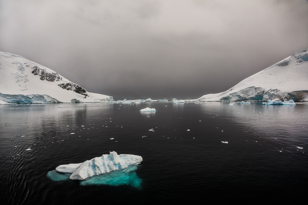 Gentle, grey light illuminates a small iceberg off the coast of Curverville Island, Antarctica.
