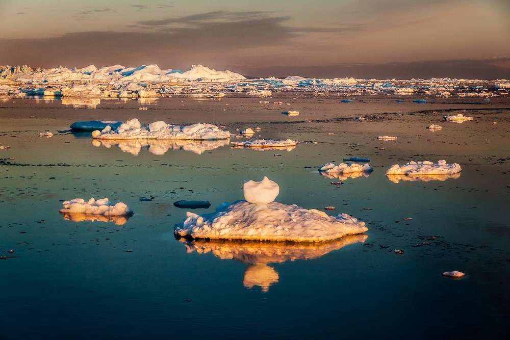 The Spectacular colors of the midnight sun illuminating icebergs in the ilulissat Icefjord, Greenland.