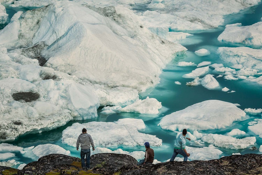 Three local inuit men on the edge of the wild near Ilulissat, Greenland.