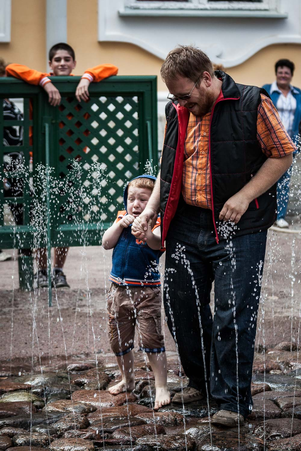 A young boy, surprised by water sprouting from the ground at Peterhof Palace near St. Petersburg, Russia.