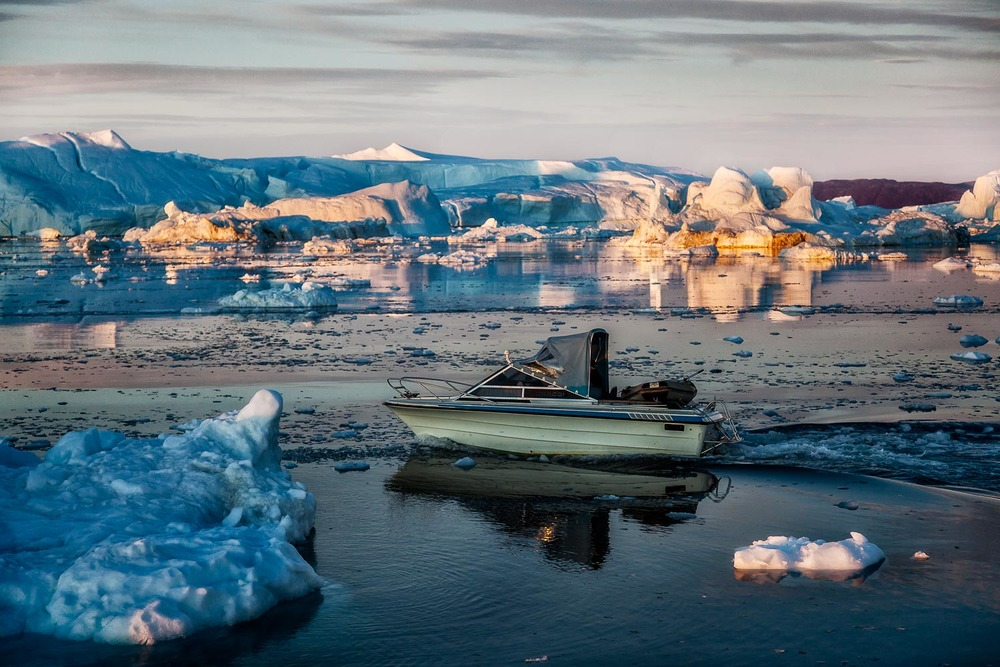 A small fishing boat heads out onto the waters of the Ilulissat Icefjord near Ilulissat, Greenland.