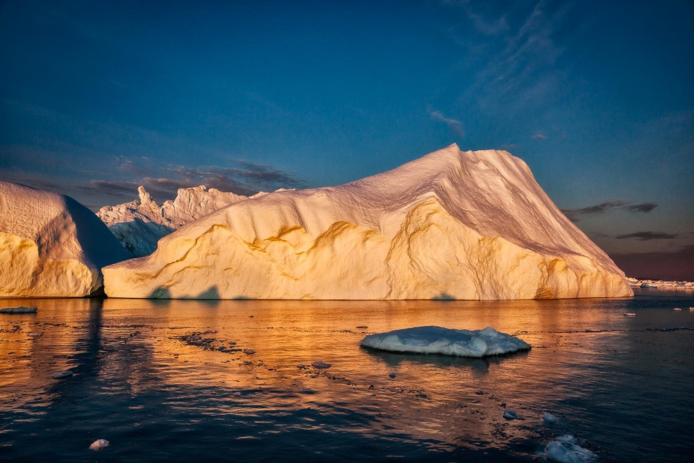 Icebergs illuminated by the midnight sun on the Ilulissat Icefjord near the town of Ilulissat, Greenland.