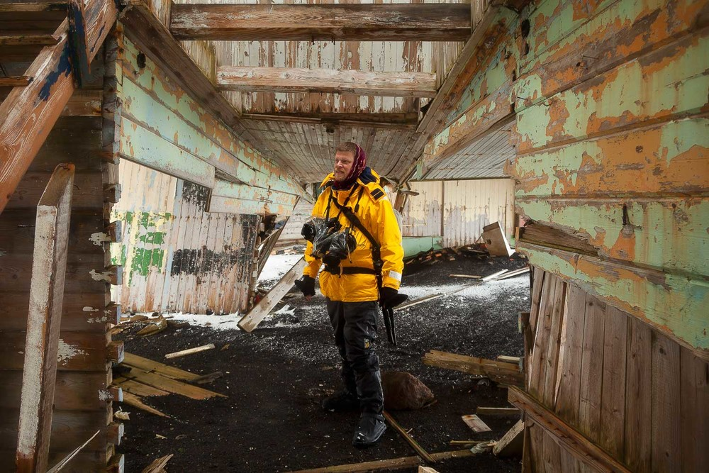 David Burren in the ruins of a building at Port Foster on Deception Island in the South Shetland Island Group, Antarctica.