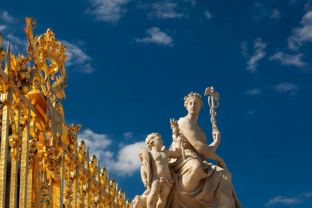 Striking light illuminates statues and the golden gate at the Palace of Versailles, France